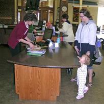 A librarian helps a mom and toddler check out books at the library.