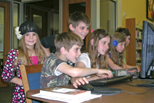 A group of children crowding around a library computer.